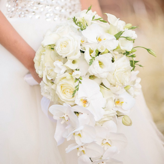 "Kelly says she ""wanted something out of the ordinary,"" so she chose a cascade-shaped bouquet of all-white flowers."