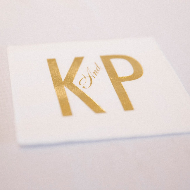 The couple put a non-traditional monogram on cocktail napkins. While they mainly stuck to a white color palette, hints of gold appeared throughout the event.