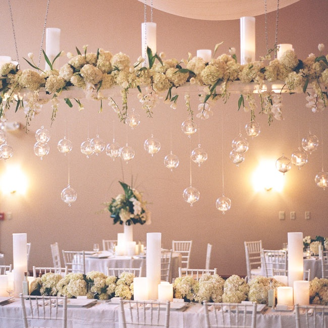 White flower arrangements, candles and glass orbs filled with tealights and flower petals hung above the head table.
