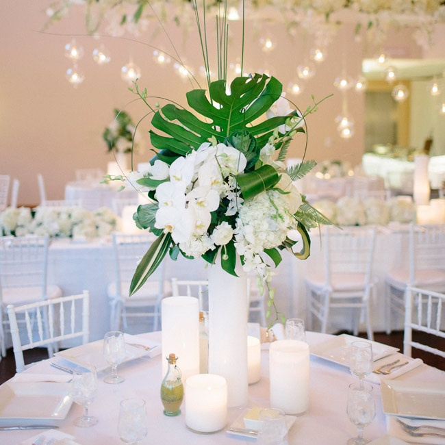 The centerpieces overflowed with white blossoms and large green leaves.