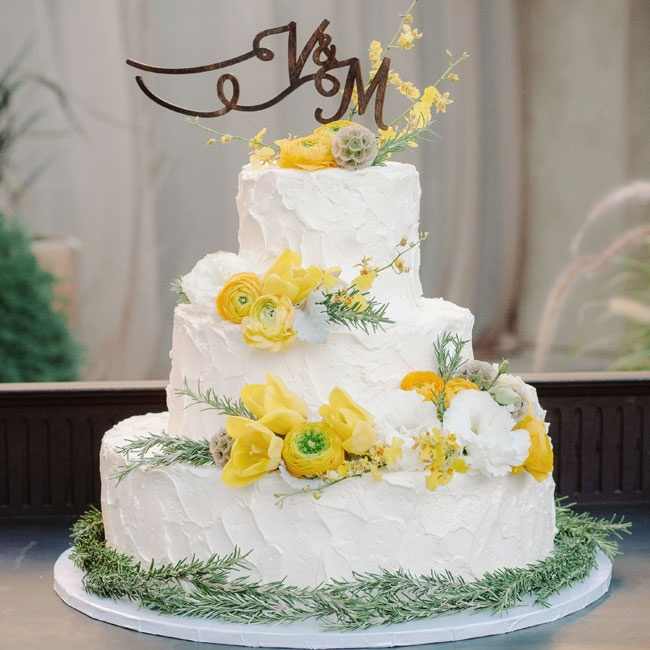 Yellow ranunculuses and tulips added a bright pop of color to the white buttercream cake, while sprigs of pine and scabiosa pods gave the cake a rustic, woodland vibe.