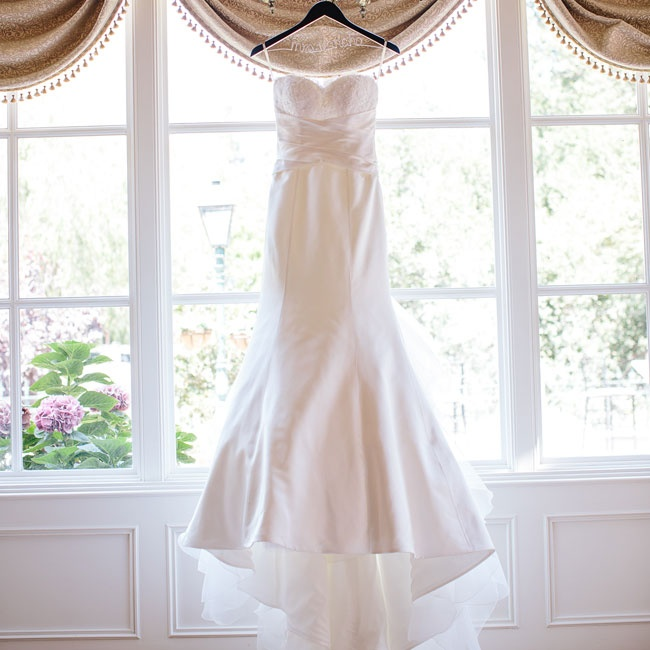 Renee's gown was a classic satin fit-and-flare style by Paloma Blanca with a sweetheart neckline, draped bodice and a ruffled chapel-length train.