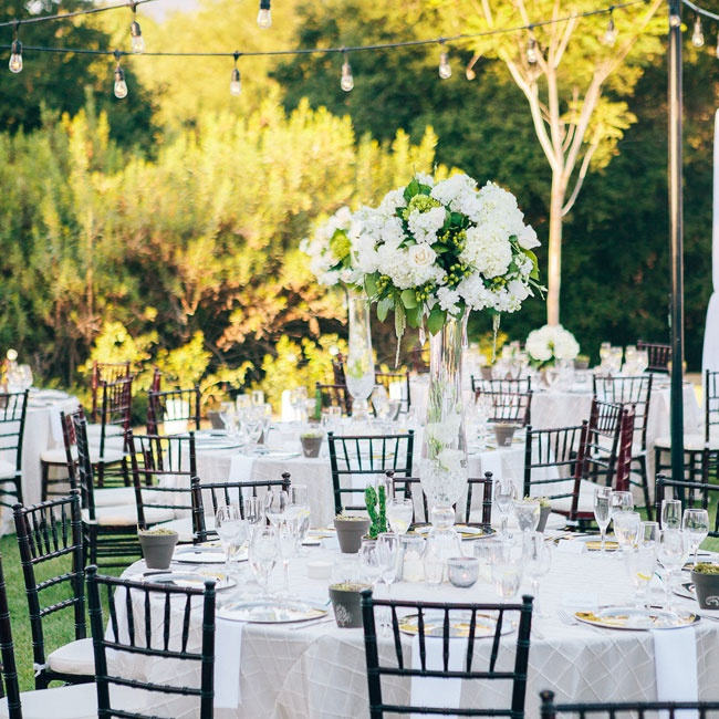 "The reception took place in backyard of Renee's family home in Coto de Caza, California. The lush greenery of the space was the inspiration for the wedding's ""Secret Garden"" theme. To highlight the beauty of the space, the couple stuck with a white and ivory color palette, adding in pops of silver and dark green for a hint of color. Tall centerpiec ..."