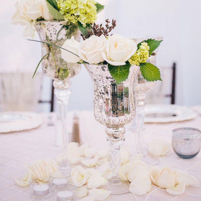 Mercury glass pedestal vases were filled with ivory roses and green hydrangea for simple-yet-elegant centerpieces. Rose petals were scattered across the table for a romantic touch.