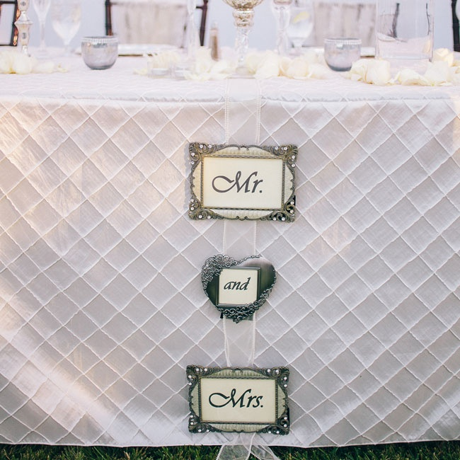"A framed ""Mr. and Mrs."" sign hung from the front of the head table where the newlyweds sat."