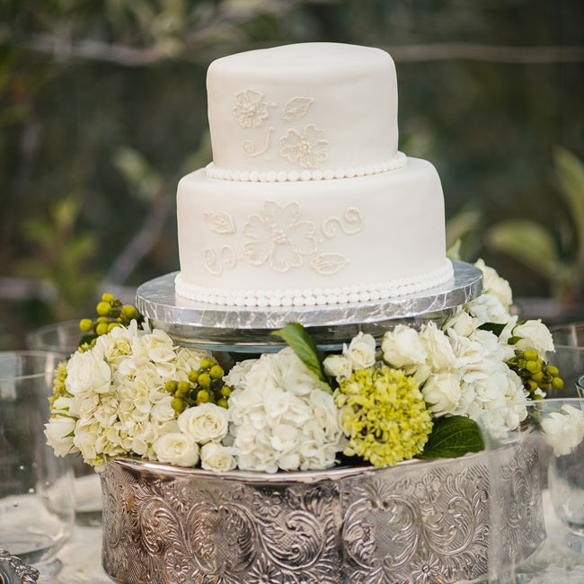 The simple two-tier cake was displayed on a decorative silver cake stand with bunches of fresh ivory roses and hydrangeas.