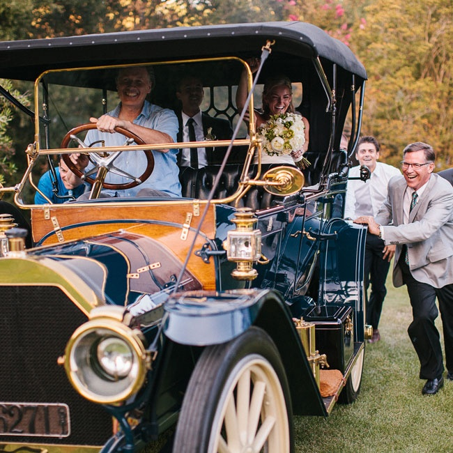 "The couple made their grand entrance in an antique car - not without some difficulty. ""Right when we got to the point where all of the guests could see us, the car got stuck on a hill and wouldn't budge. Ten to fifteen guests jumped out of their seats and ran to push the car up the hill. IT ended up being a really special moment and makes us laugh  ..."