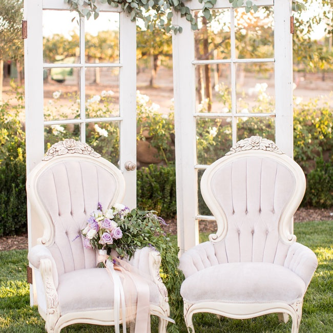 Pale lavender Louis XV chairs and an upcycled French door backdrop added an elegant, shabby-chic flair to the decor.