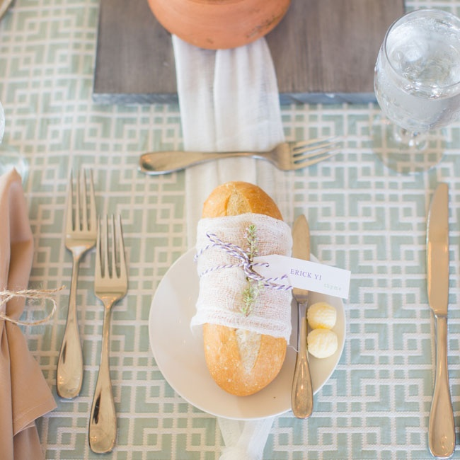 Loaves of fresh bread wrapped in gauzy white fabric and tied with lavender striped string was placed at each seat.