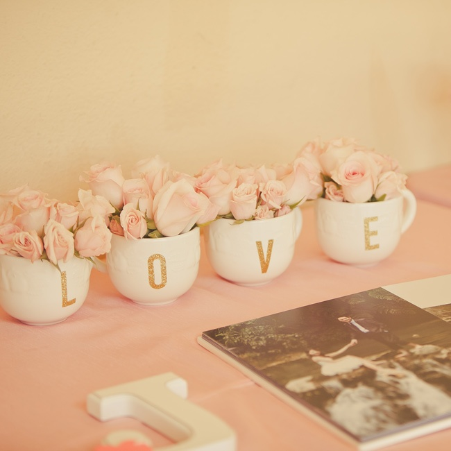 "White mugs spelling out ""love"" in gold glitter were filled with pale pink roses and placed on the guestbook table."