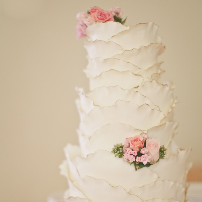 The couple's cake was covered in white chocolate ruffles and delicate pink flowers. They chose unique flavors for the cake, like apple spice and lemon curd.