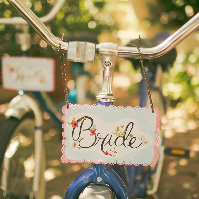 "The bride and groom made their exit on blue beach cruisers with handmade bride and groom signs on the front and a ""Just Married"" sign on the back."