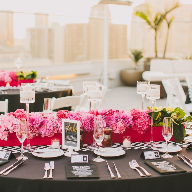 The tables were set with black linens, chevron table runners and bright floral centerpieces. Vibrant pink roses, dahlias and hydrangeas were arranged in red planter boxes that stretched the length of the tables.