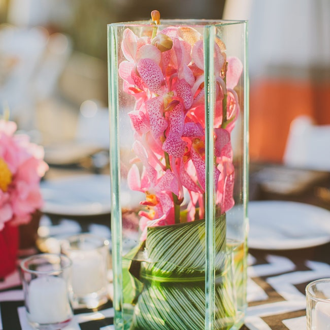 "Tall glass vases filled with bright pink orchids and tropical foliage brought a ""West Coast"" look to the tablescapes."