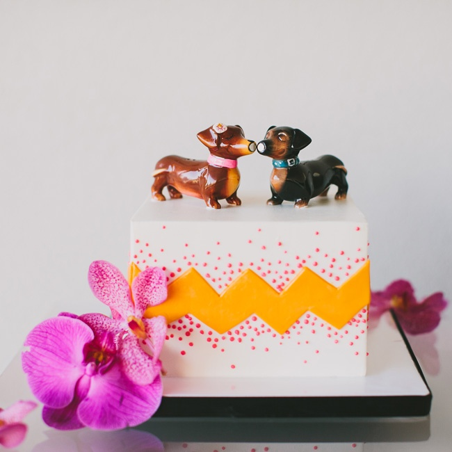 Instead of a traditional cake, Christine and Rich opted for a funky square cutting cake with orange chevron, pink dots, fresh orchids and a dachshund cake topper in honor of their dog Brody.