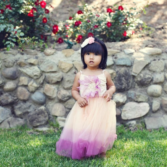 The flower girl wore a purple and peach-colored chiffon dress with a large floral embellishment on the bodice.