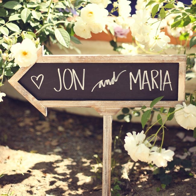 A chalkboard sign in the shape of an arrow pointed the way to the ceremony.