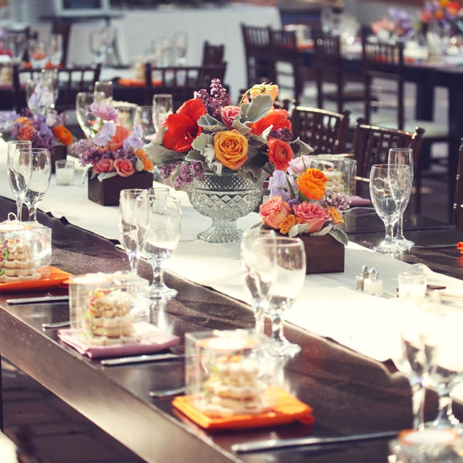 Bright orange roses, red ranuculuses and silvery dusty miller were arranged in crystal pedestal vases and wood planter boxes along the length of the table, adding a fresh pop of color to the tablescapes.