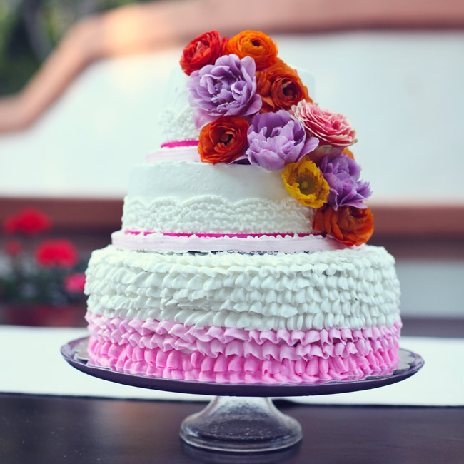 Maria's mother, a former baker, made the couple's three-tier buttercream cake. She decorated the cake with cascades of vibrantly colored flowers and ombre ruffles to give the cake a playful look.