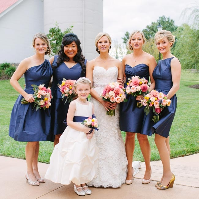 Cocktail length navy dresses in the same color and fabric but different styles looked cohesive but allowed the bridesmaids to feel comfortable.