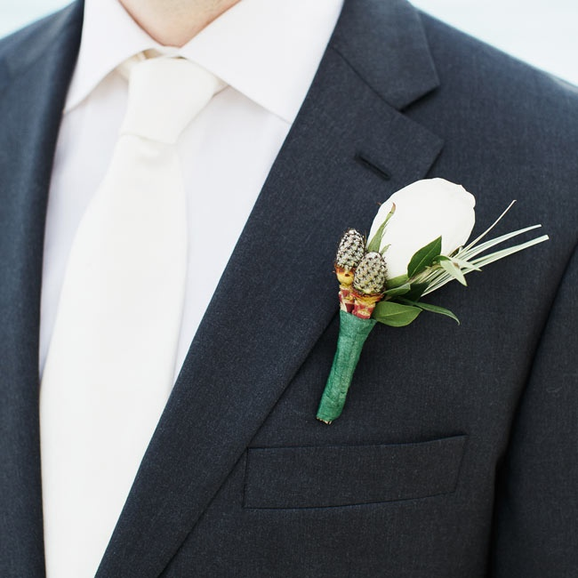 The groom accessorized his dark suit with a white tie and a matching white rose boutonniere.
