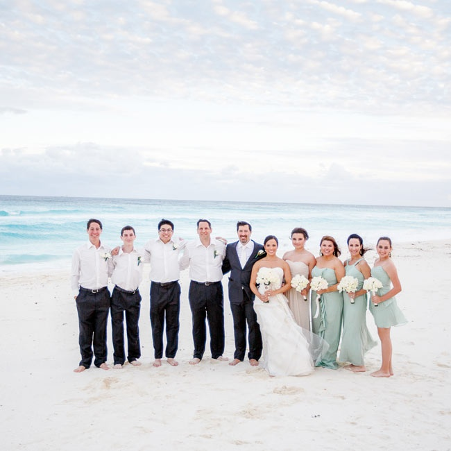 The wedding party went barefoot at the beach ceremony but bridesmaids were clad in light sage dresses, while the maid of honor's dress was a neutral tan. Groomsmen wore dark slacks with classic Oxford shirts.