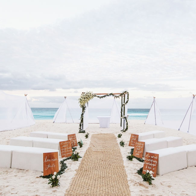 Deborah and Larry's simple beach ceremony incorporated long white benches with painted wooden signs lining each aisle and pitched tents surrounding the entire area for a feeling of exclusivity.