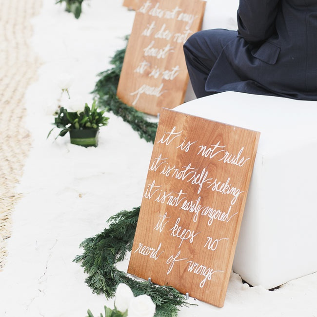 Simple wooden signs were placed at the end of each aisle with traditional quotes about love's nature painted in a handwritten script.