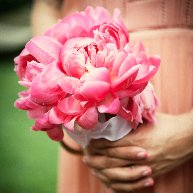 The bridesmaids carried small bouquets of vibrant pink peonies.