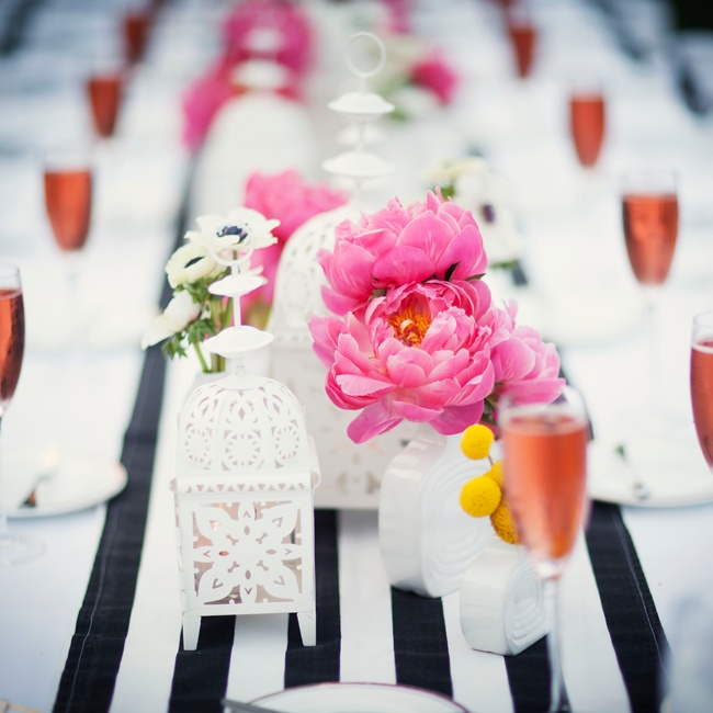 Black-and-white striped table runners added a modern touch the tablescapes. White metal lanterns and bright anemones and billy balls were scattered the length of the table.