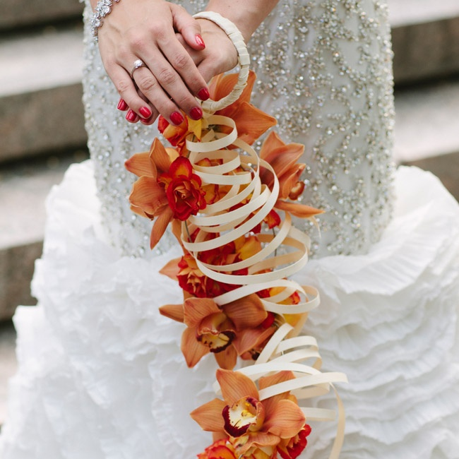 "The bride didn't want to carry a traditional bouquet (""I really don't like carrying things — I avoid purses at all costs,"" she says), so a cascade of orange orchids hung from a cuff on her wrist instead."