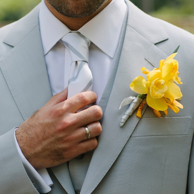 Roby's three-piece, light gray suit got a pop of color from a bright yellow orchid. The groom also accessorized with monogram cufflinks and superhero-themed socks.