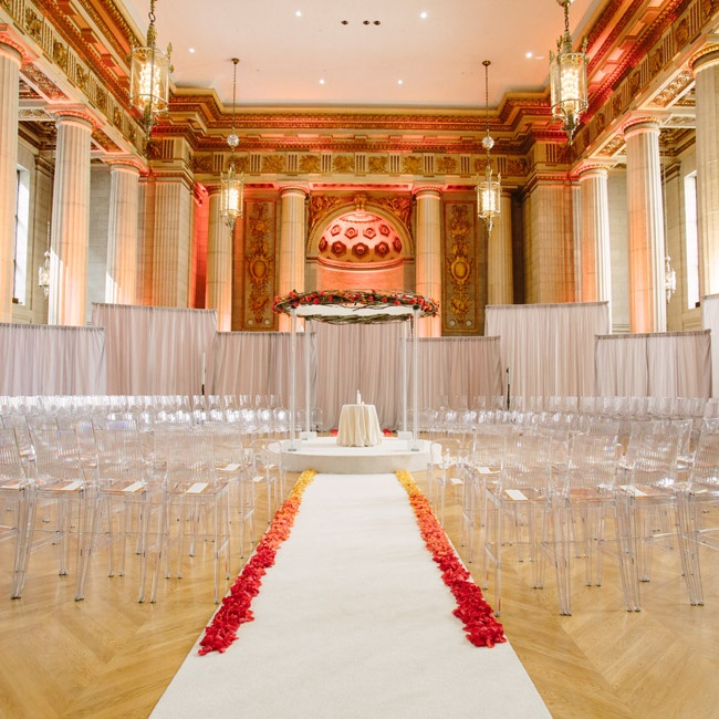 The ceremony space, the Andrew W. Mellon Auditorium, was decorated with ombre flower petal aisle liners, gray drapery as dividers to make the space feel more intimate and a round huppah with branches and red flowers.