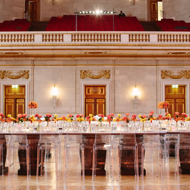Tables were mounted on boubon barrels, which added just a hint of rustic detail to the otherwise luxe affair. Red, yellow and orange flowers complemented the ballroom's gold and burgundy details.