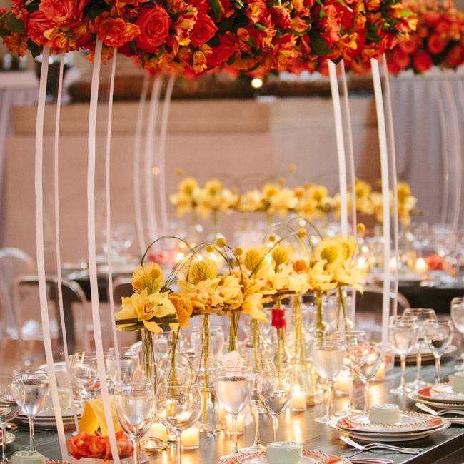 Bourbon bottles filled with yellow orchids and connected by reeds sat on the tables, while arrangements of red and orange roses and parrot tulips towered above them.