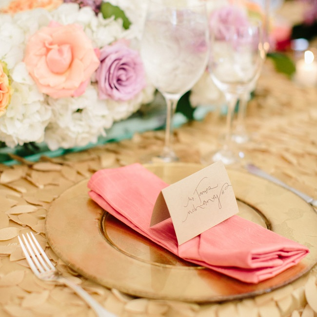 Coral napkins added a pop of color amongst the gold tablecloths, chargers and place cards.