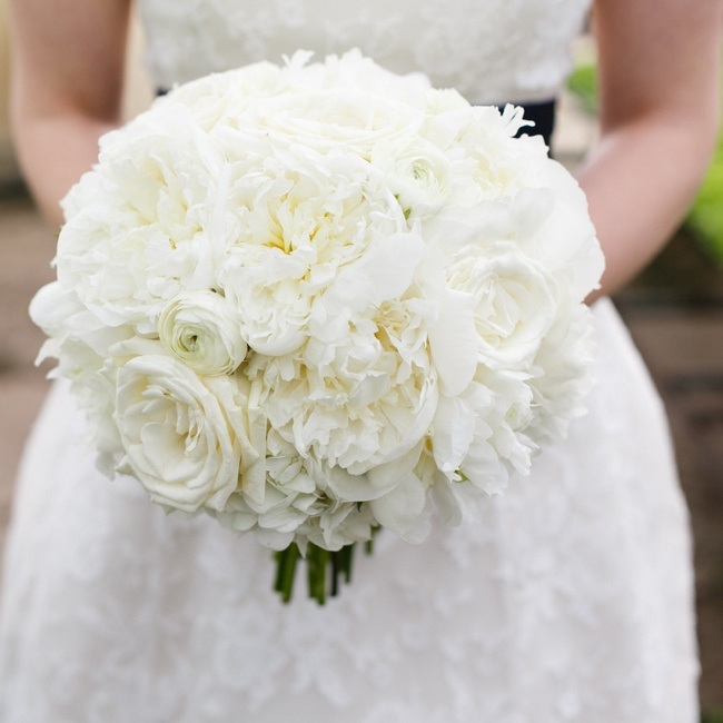 The bride carried a lush bouquet of all-white peonies, roses and ranunculuses.