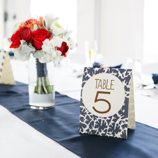 The centerpieces matched the bridesmaids' bouquets, while the simple table numbers matched the patterns on the escort cards and other decor.
