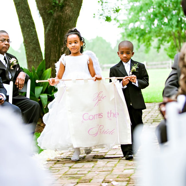 The child attendants wore attire similar to the bridal party with the ring bearer in a black tuxedo and the flower girl in an organza dress and angel wings.