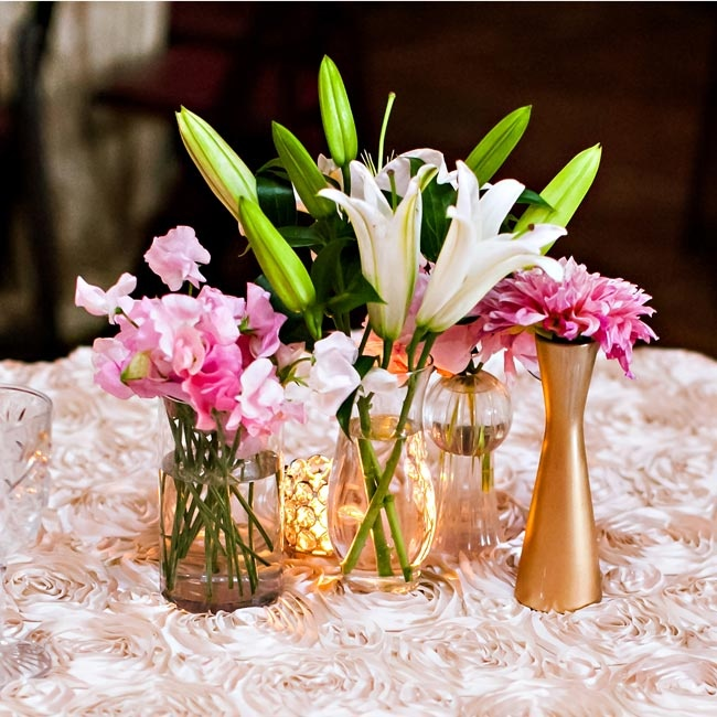 A combination of clear and gold vases held pink and white blooms. The arrangements sat atop lush table linens in a stunning rosette pattern.