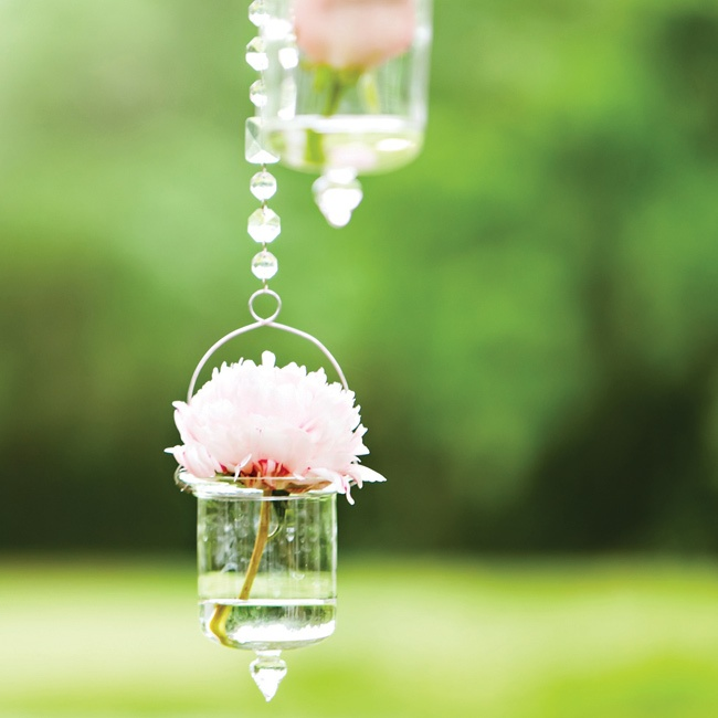 The couple married under a white arbor that was hung with crystals and votives that held various pink blooms.