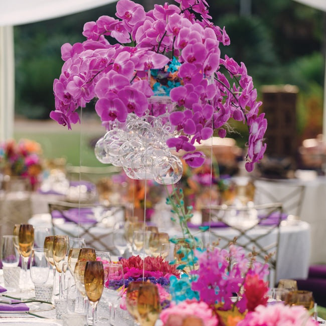 Large orchid chandeliers hung from the ceiling of the tent and became floating centerpieces. Glass globes with votive candles inside lit the blooms from below.