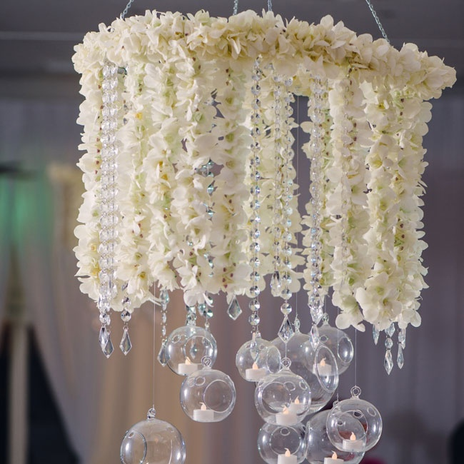 White orchid and crystal chandeliers hung from the ceiling and added a soft glow courtesy of the globe votives that hung below.