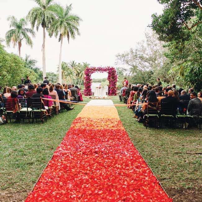A gorgeous ombré aisle of rose petals led to the ceremony mandap (altar), which was decorated in magenta bougainvillea, jasmine and hanging strands of hot pink dendrobium orchids.
