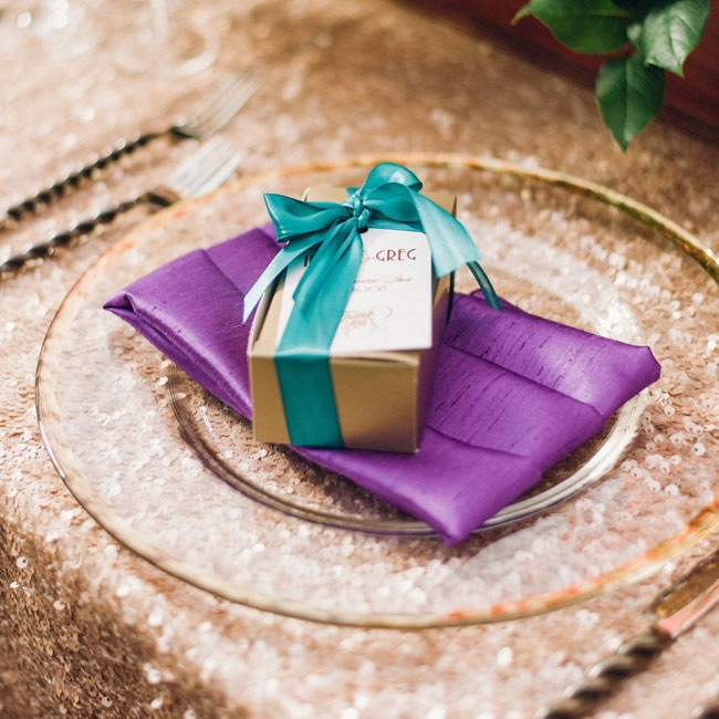 Small gold favor boxes were tied with teal ribbons and sat atop purple napkins at each place setting.