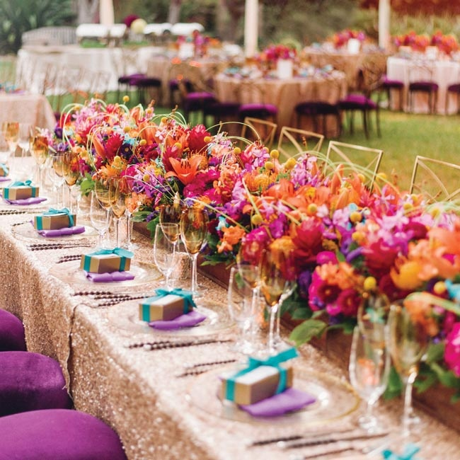 The flowers were the star at this outdoor wedding. A low, dense floral arrangement of hydrangeas, red ginger, orchids, yellow yarrow, craspedia, matsumoto asters, orange lilies, jasmine and pincushion proteas ran the
