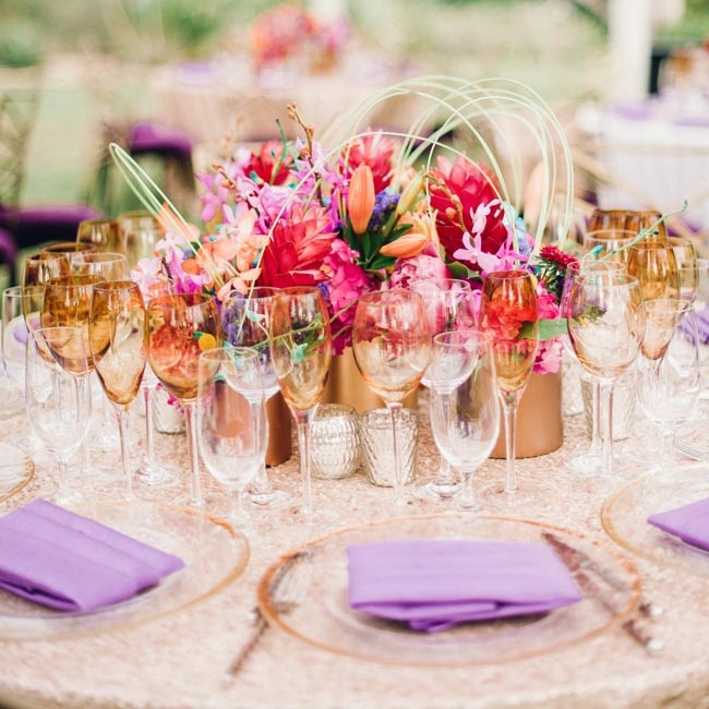 Petite gold vases held vibrant-colored blooms in small clusters. The entire look was pulled together with loops of bear grass around the top.