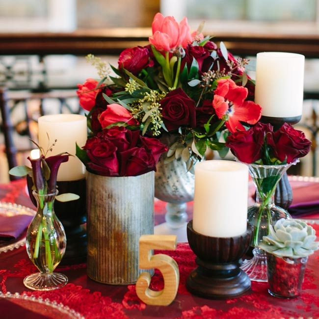 The tables were topped with multiple small arrangements and bud vases filled with garden roses, tulips, succulents and ranunculuses all in shades of red and eggplant.