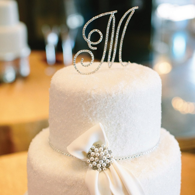 Molly didn't really want a cake, so she asked her mother to choose one. The result was a white, two-tiered confection decorated with a bow and brooch that matched the bride's dress.