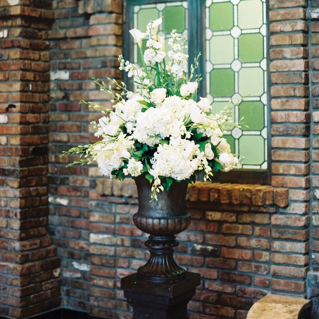 Large antique urns filled with white roses, hydrangeas and calla lilies complemented the ceremony space without competing with the bold architecture.
